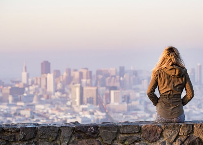 young girl sitting on wall overlooking big city